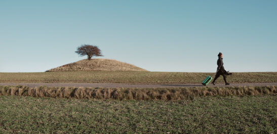 Girl dragging a suitcase on wheels through a fild with a distinct hill with a single tree on top in the background