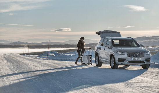 Girl loading Volvo car in the road. The setting is in northern Sweden in the sunset.